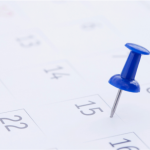 Calendar with thumbtack highlighting special days in luxury real estate.